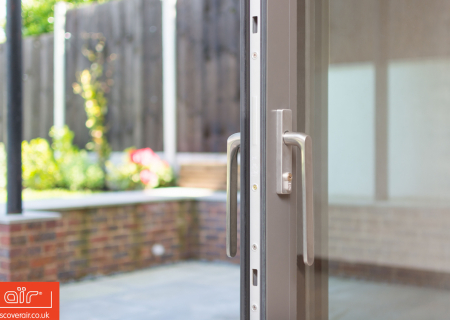 Close-up-of-an-air-lift-and-slide-door-hande-leading-into-a-Bushey-garden